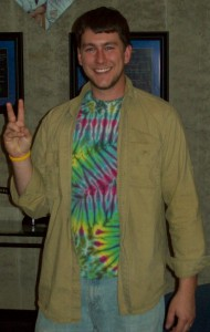 Person in tie-dye shirt making a peace sign