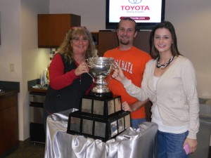 Three people posing with a trophy