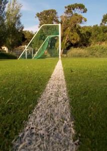 Boundary line leading to a Soccer net goal post