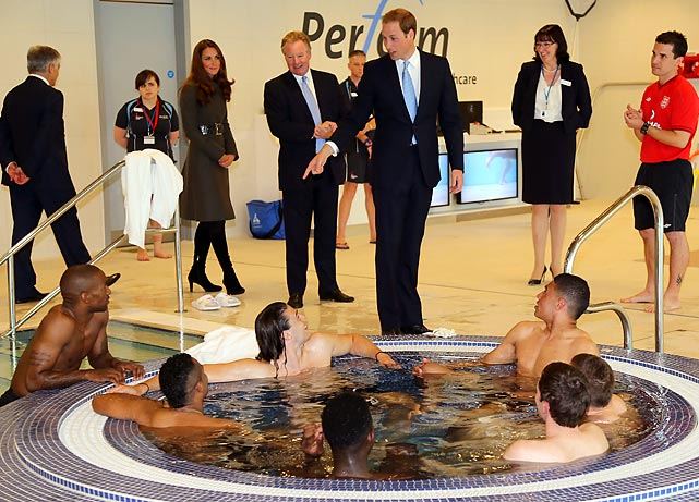 Prince William standing over group of people in a pool