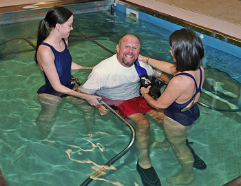 Two trainers helping person do Hydrotherapy at HydroWorx