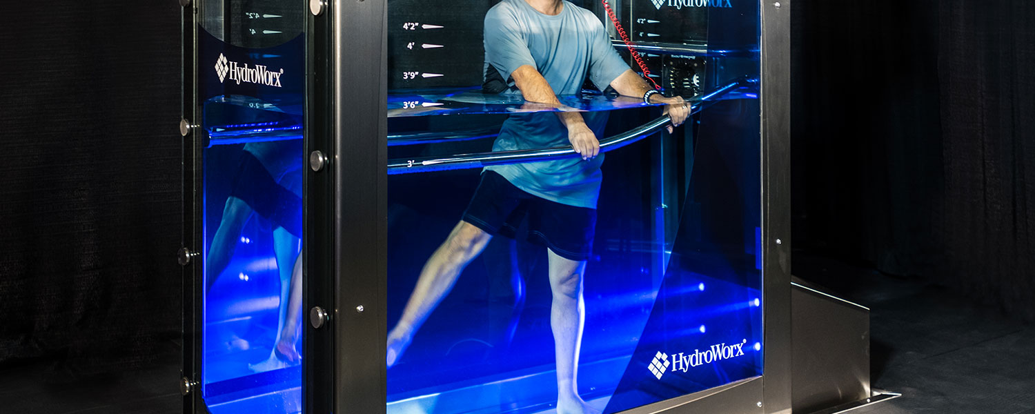 Person stretching legs underwater in HydroWorx tank