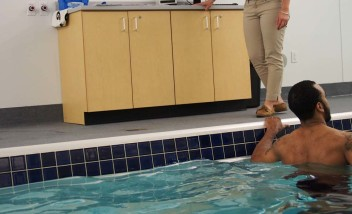 Person stretching in pool with trainer advising