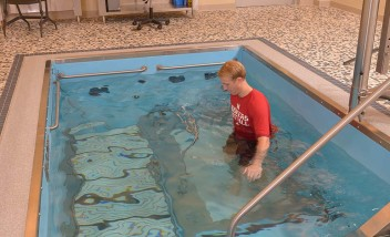 Person training in pool wearing Huskers shirt