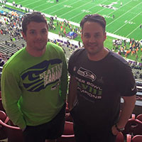 Two Seahawks fans standing at a football game