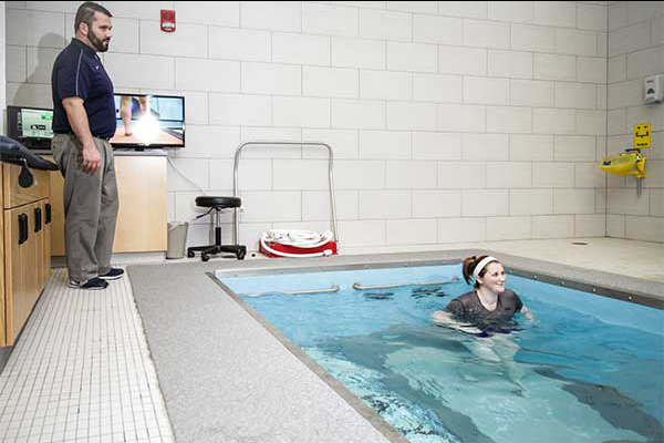 Person helping to train in HydroWorx Pool