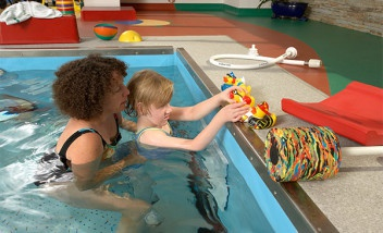 Adult holding child in pool with rubber ducks