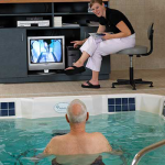 Trainer instrcuting Pool trainee with tv display
