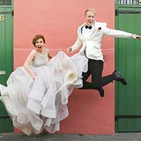 Couple in suit and dress jumping for picture