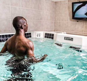 Person watching self run in pool on monitor
