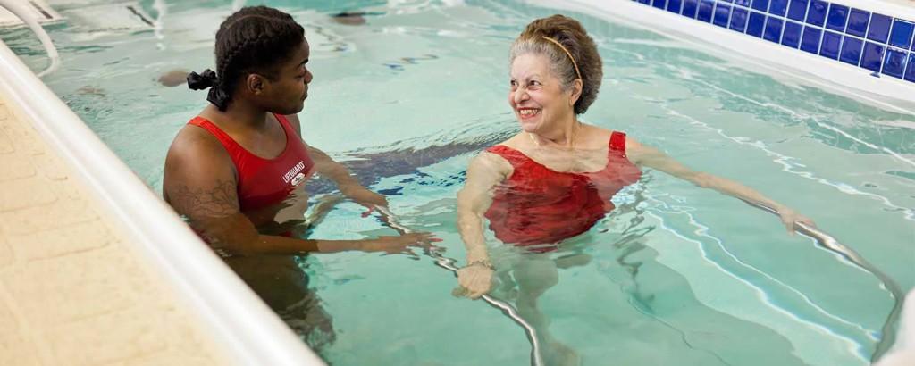 Lifeguard helping pool trainee