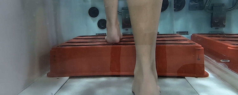 underwater view of feet walking up step